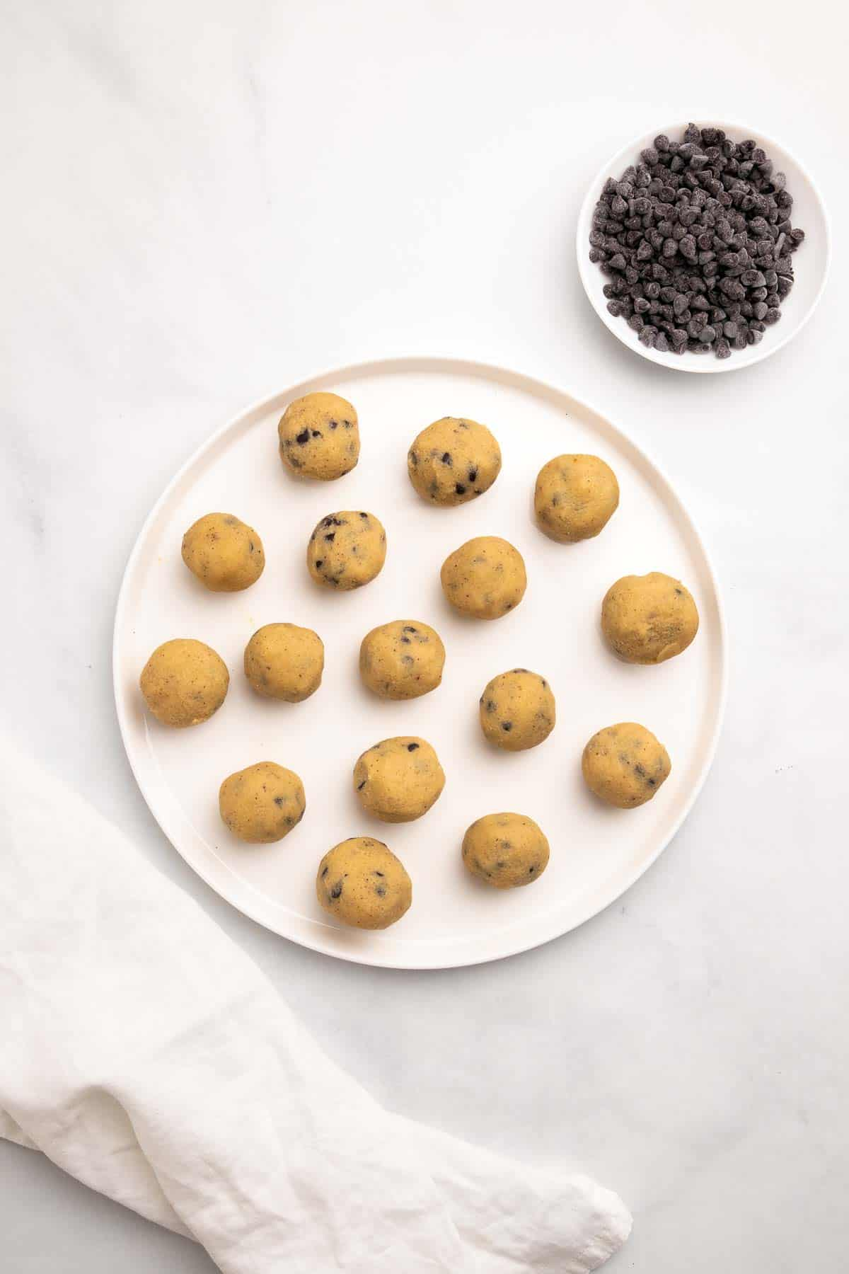 Cookie dough balls on a white circular tray next to a ramekin of chocolate chips, as seen from above