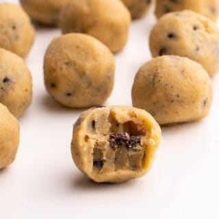Closeup of Keto Cookie Dough balls on a white serving tray with a bite taken out of one