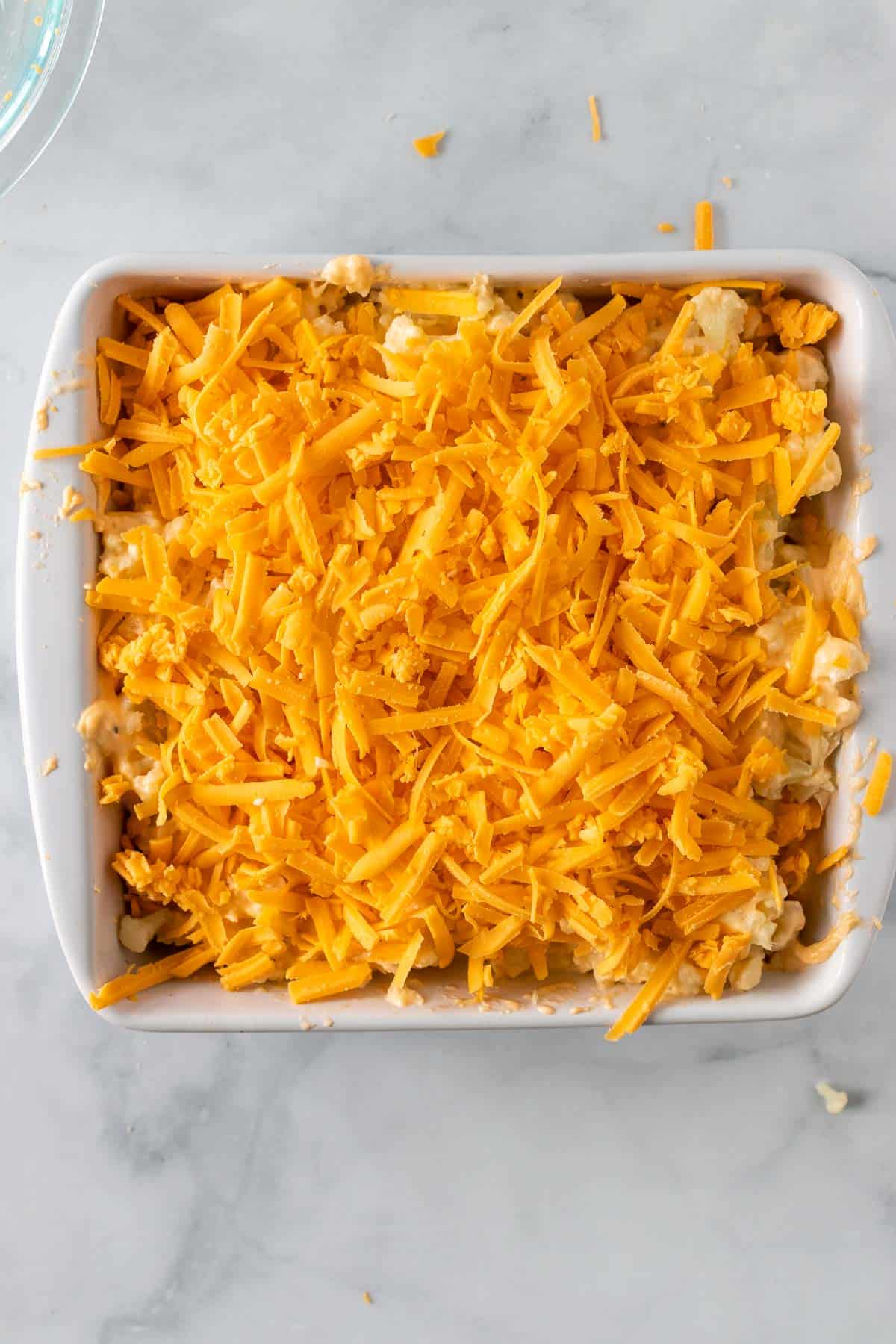 Cheddar cheese on top of the unbaked cauliflower and cheese mixture