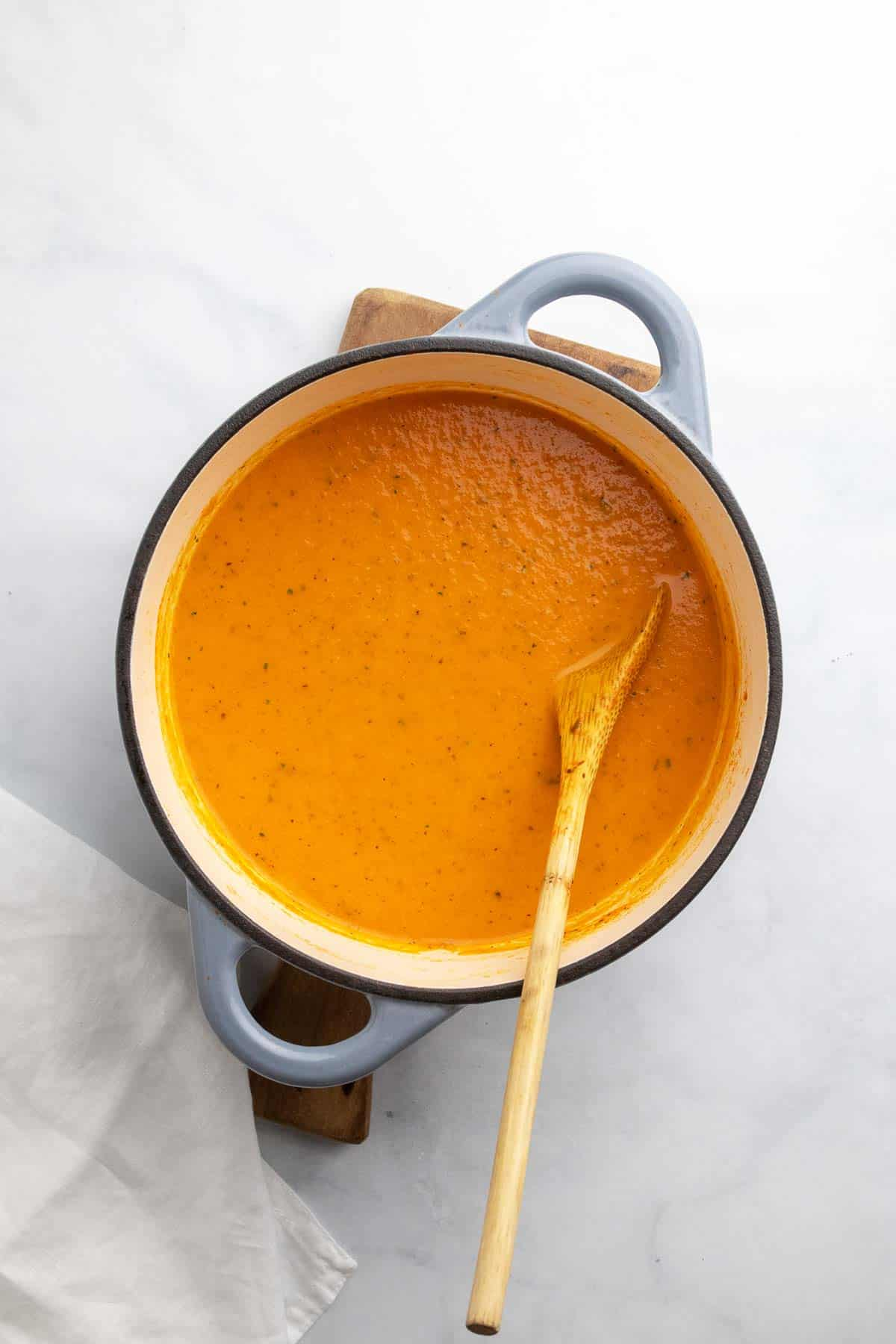 Blended soup in a heavy bottom pan with a wooden spoon