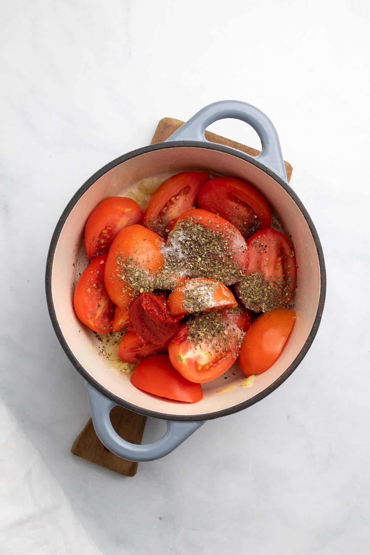 Tomatoes, tomato paste, and seasoning added to the heavy bottomed pan
