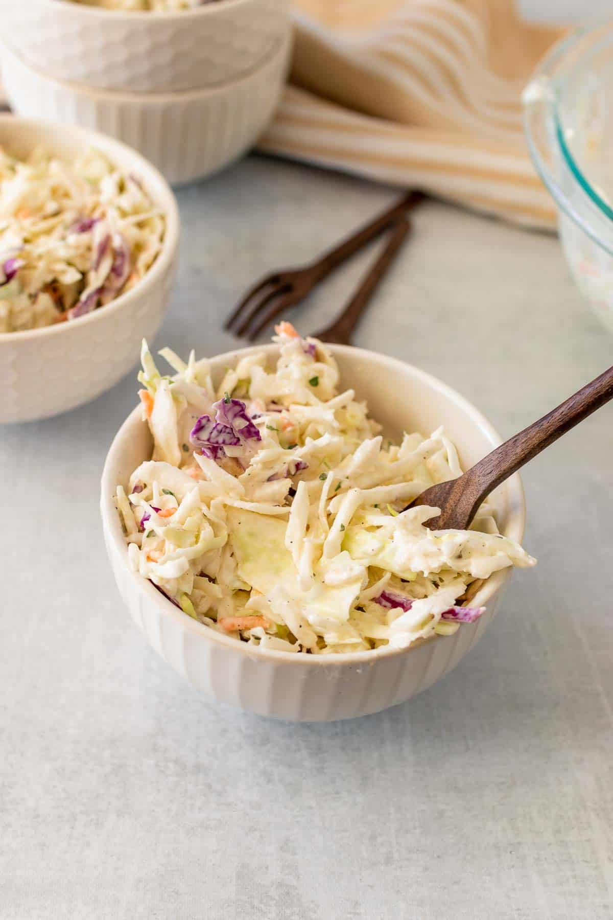 Coleslaw in a white bowl with a wooden fork