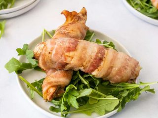 Two bacon wrapped chicken tenders over fresh greens on a white plate