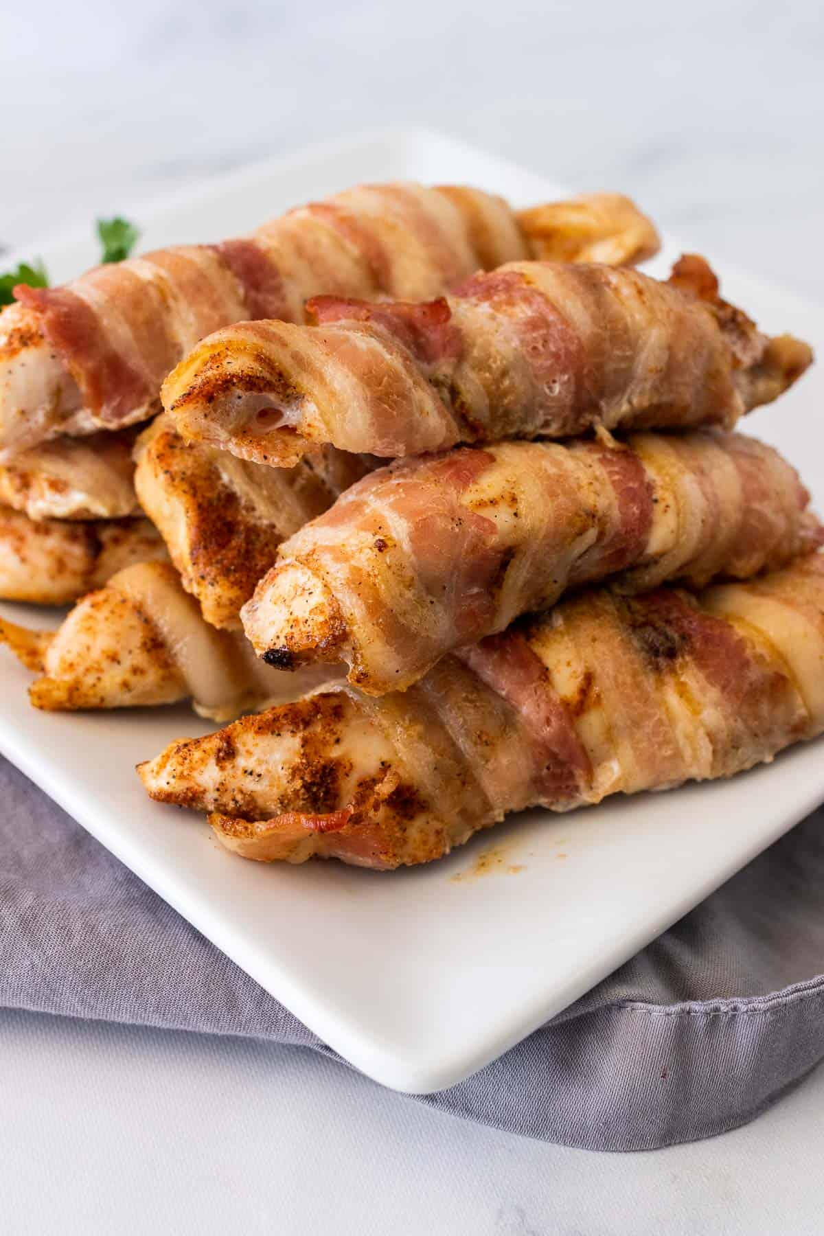 A pile of chicken tenders wrapped in bacon on a white serving plate