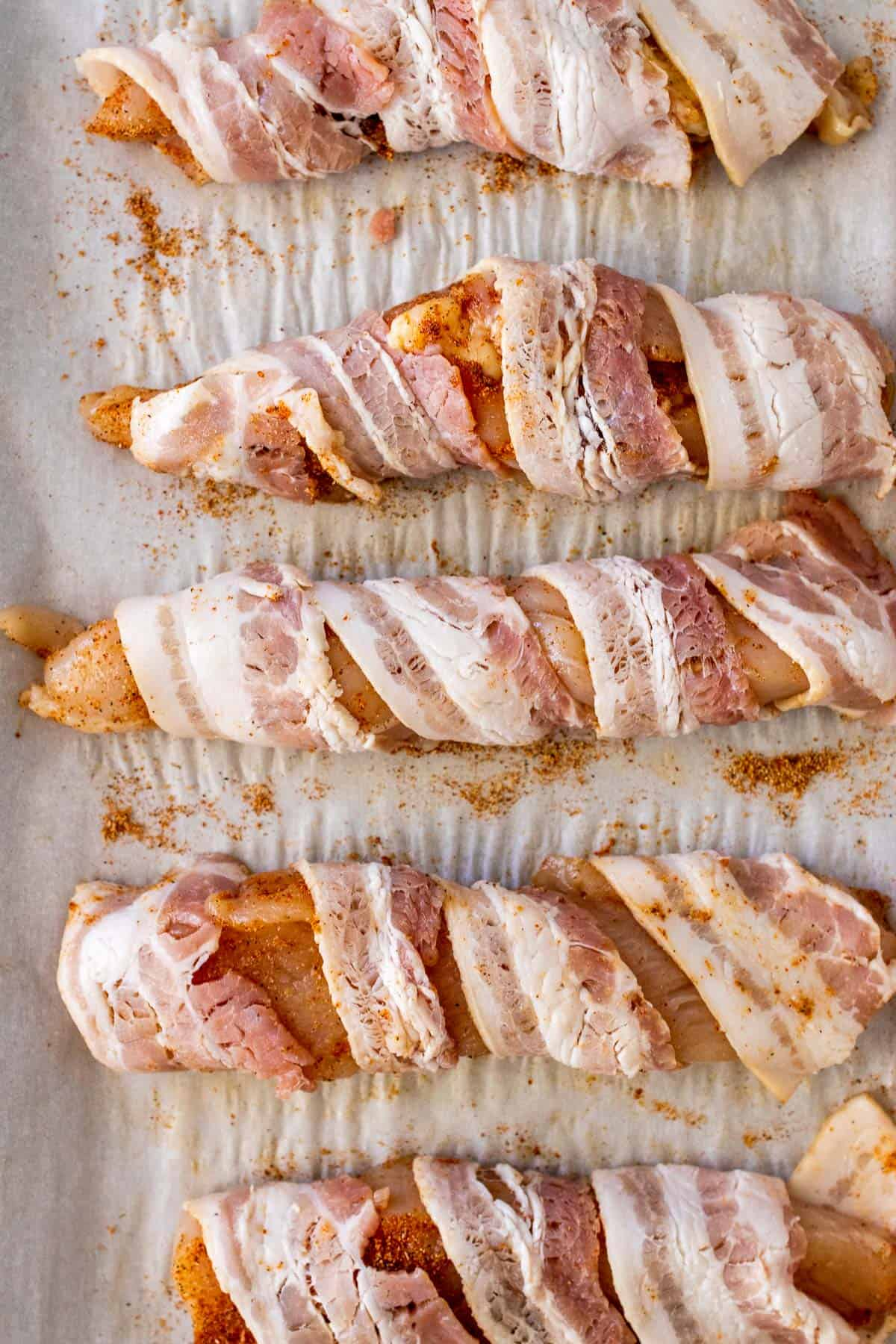 Seasoned chicken breast strips wrapped in bacon on a baking sheet, ready to go in the oven