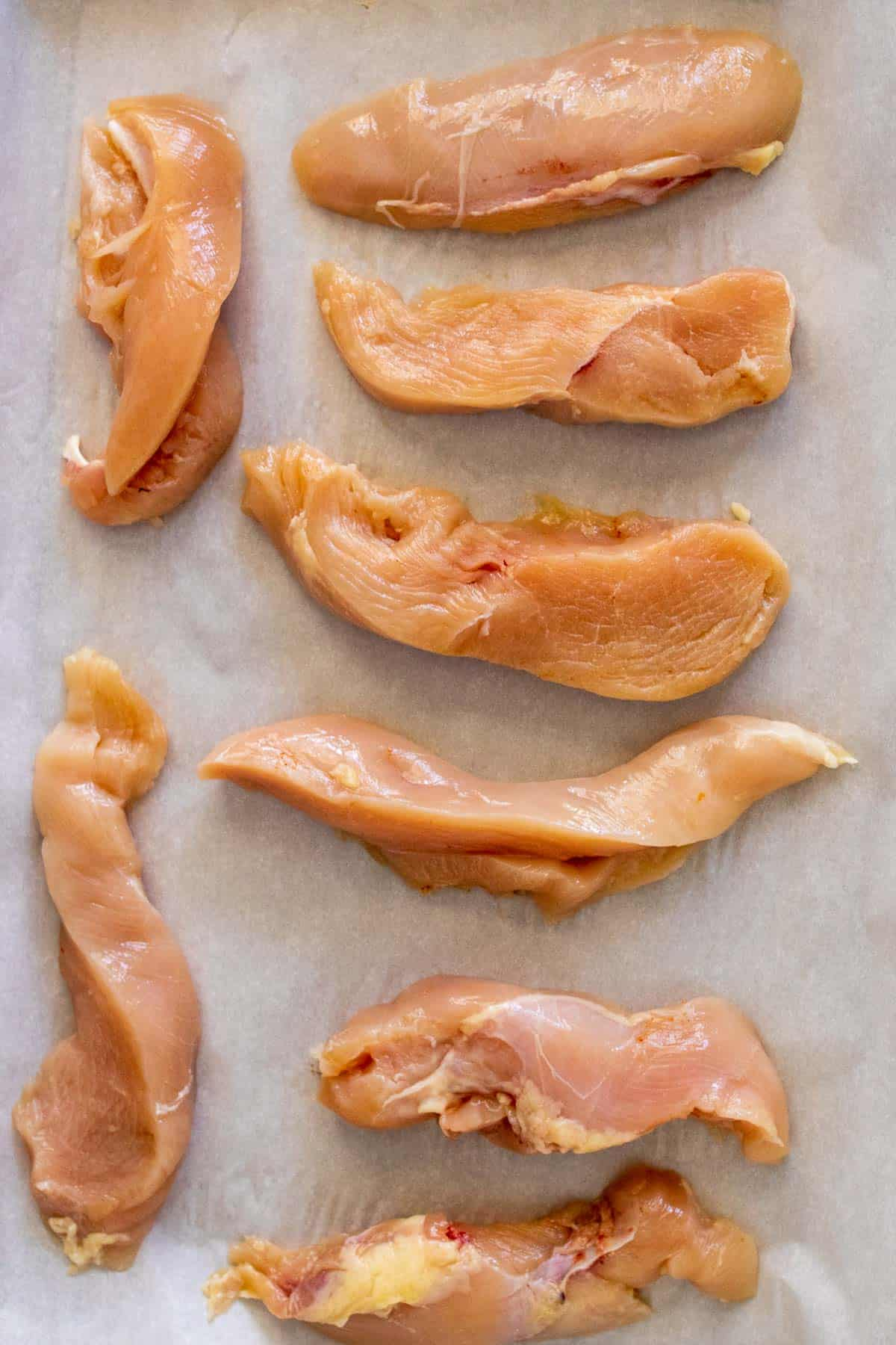 Strips of chicken breast on a baking sheet lined with parchment paper