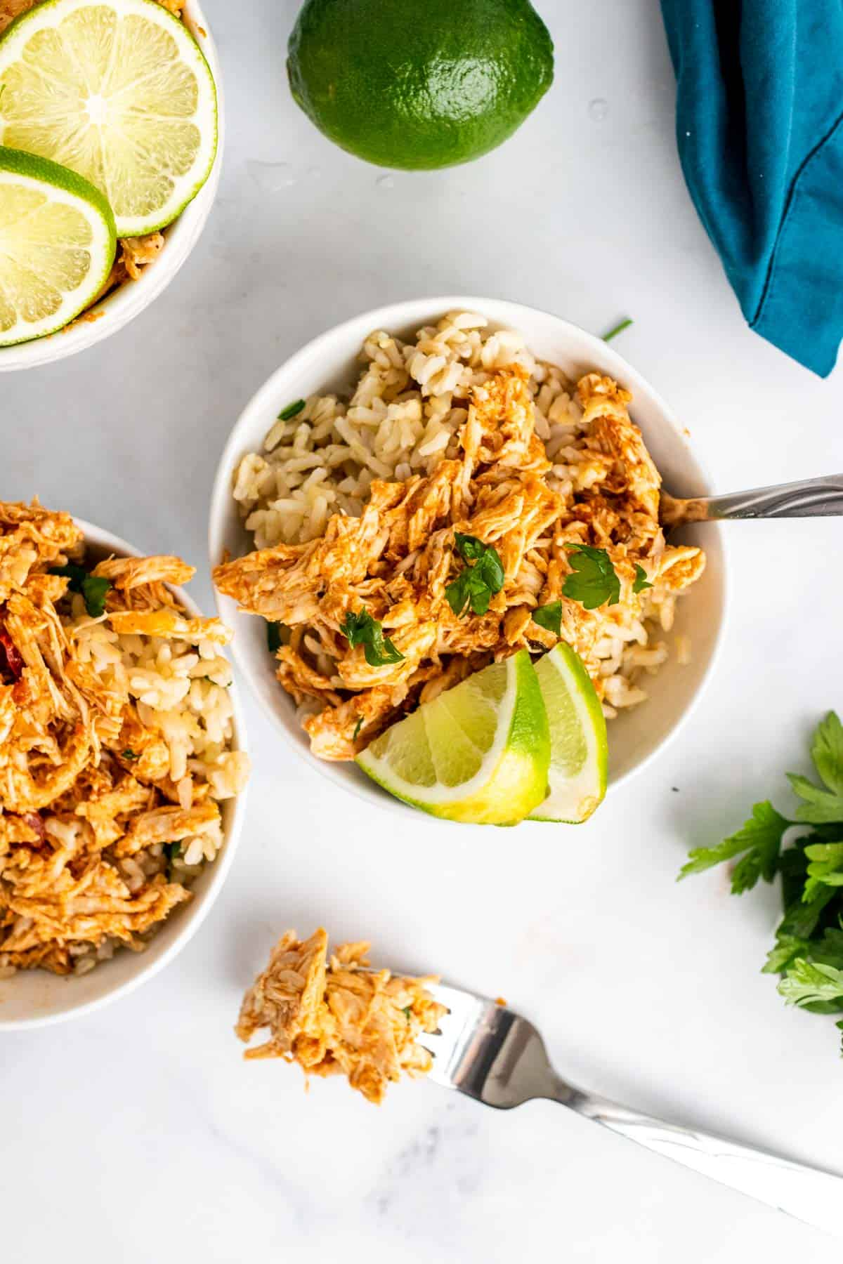 Two bowls of shredded chicken over white rice, garnished with cilantro and lime wedges, as seen from above