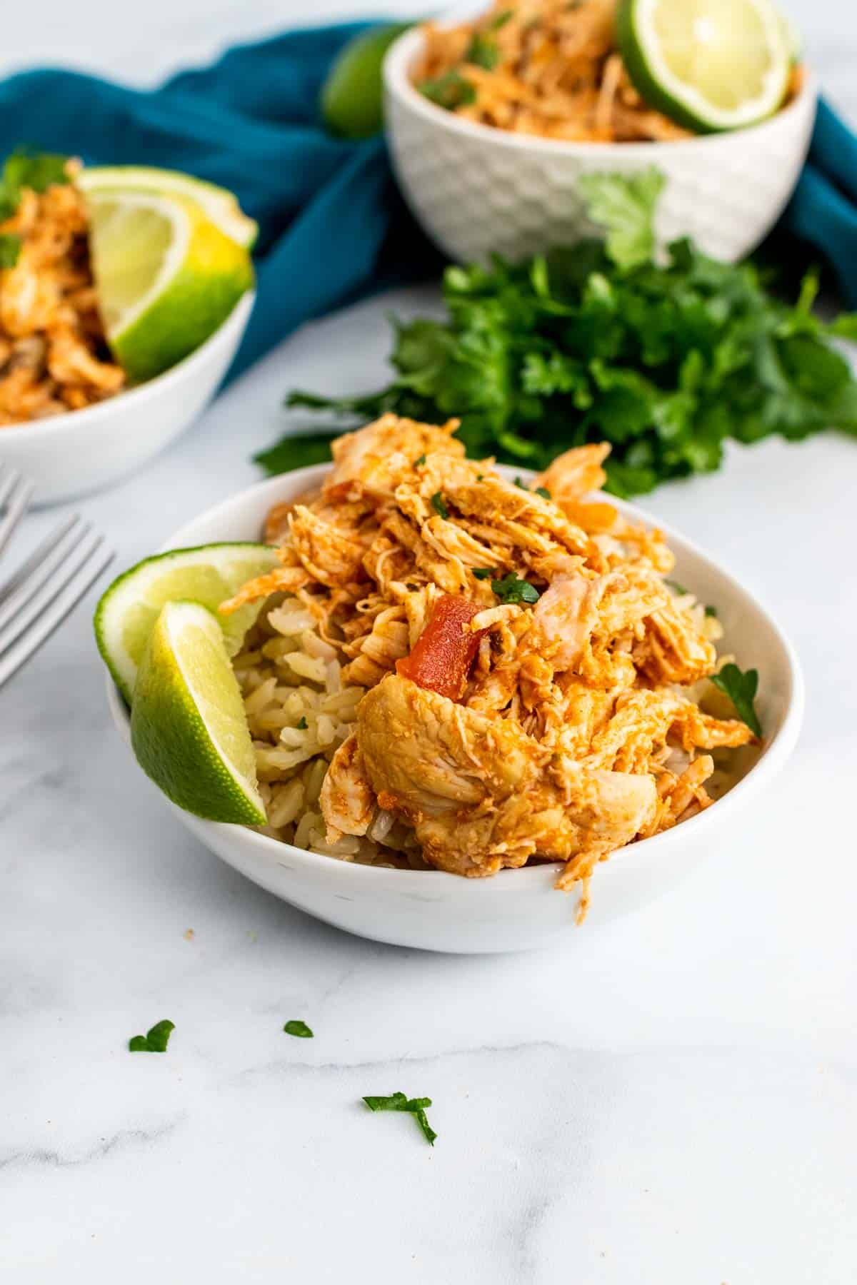 Three bowls of shredded chicken over rice with lime wedges