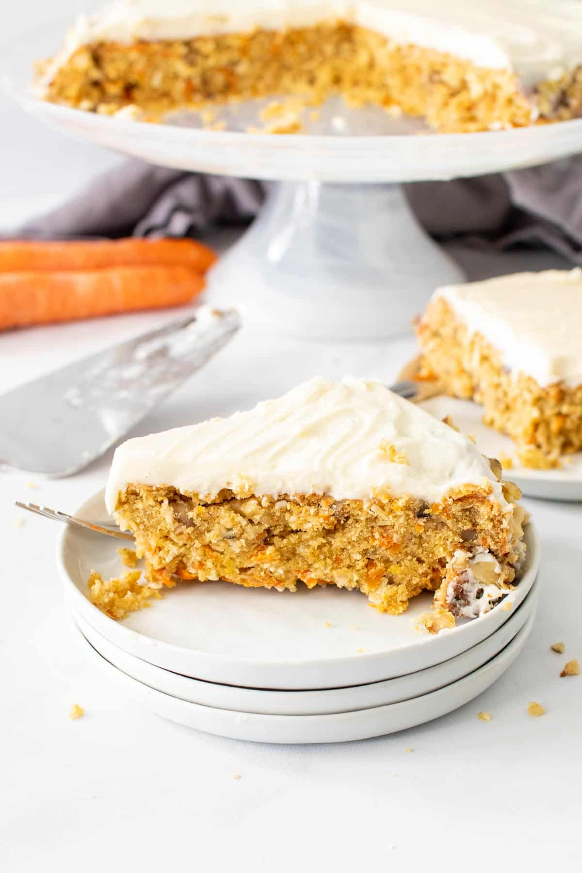 A slice of keto carrot cake on a white plate with the full cake on a cake stand in the background