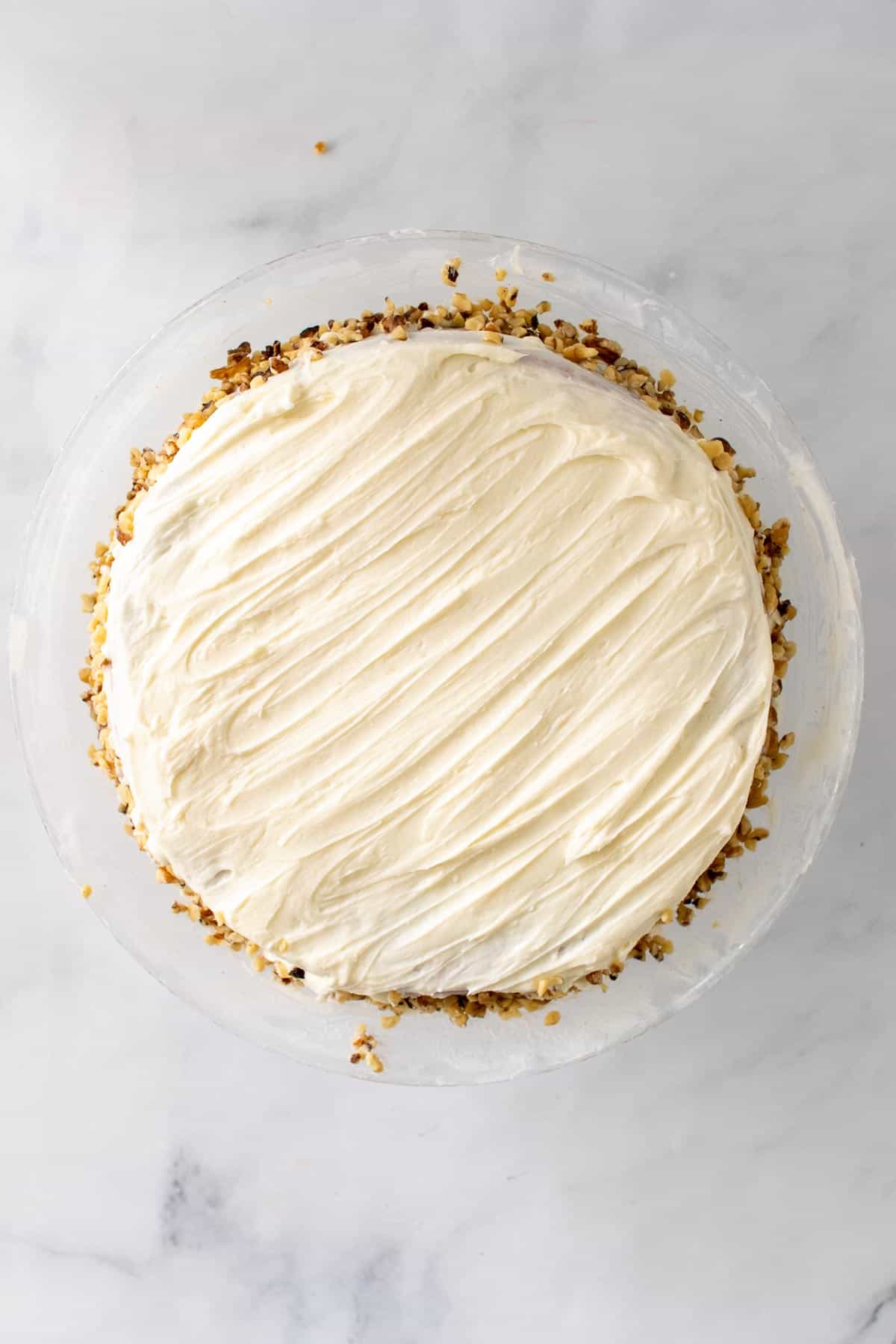 Carrot cake with cream cheese frosting on top and walnuts on the sides, as seen from above