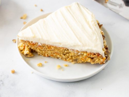 A slice of keto carrot cake on a white plate next to a serving utensil