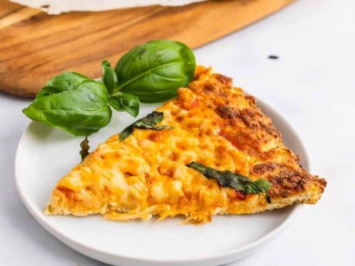 A slice of keto chicken crust pizza on a white plate next to basil leaves