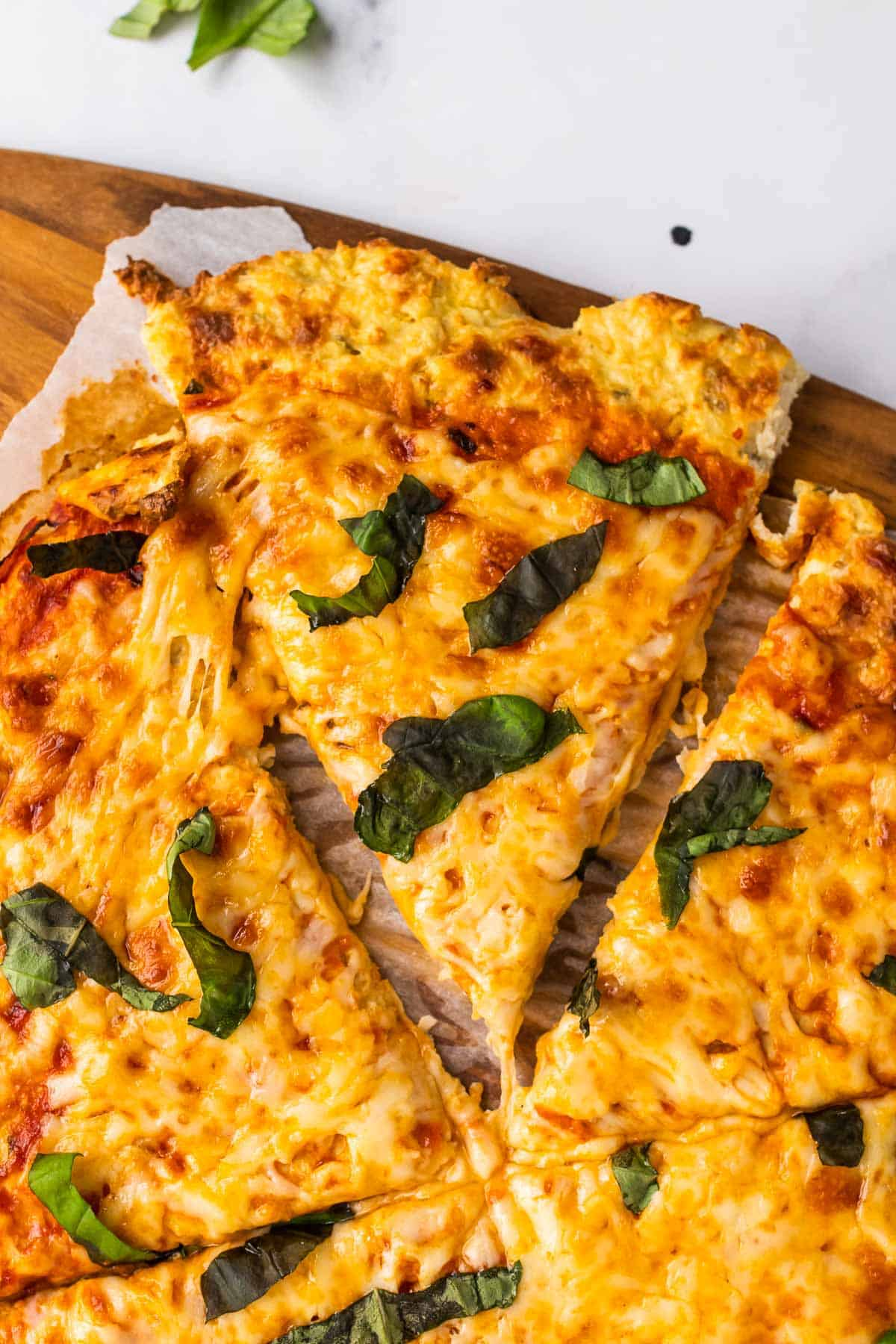 Closeup of pizza on a wooden cutting board with one slice cut out