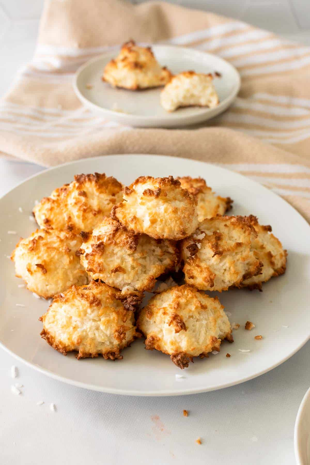 Stack of Keto Coconut Macaroons on a white plate, topped with shredded coconut