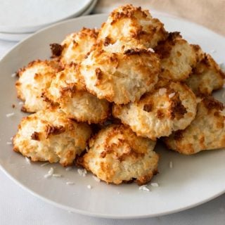 A stack of Keto Coconut Macaroons on a white plate with shredded coconut