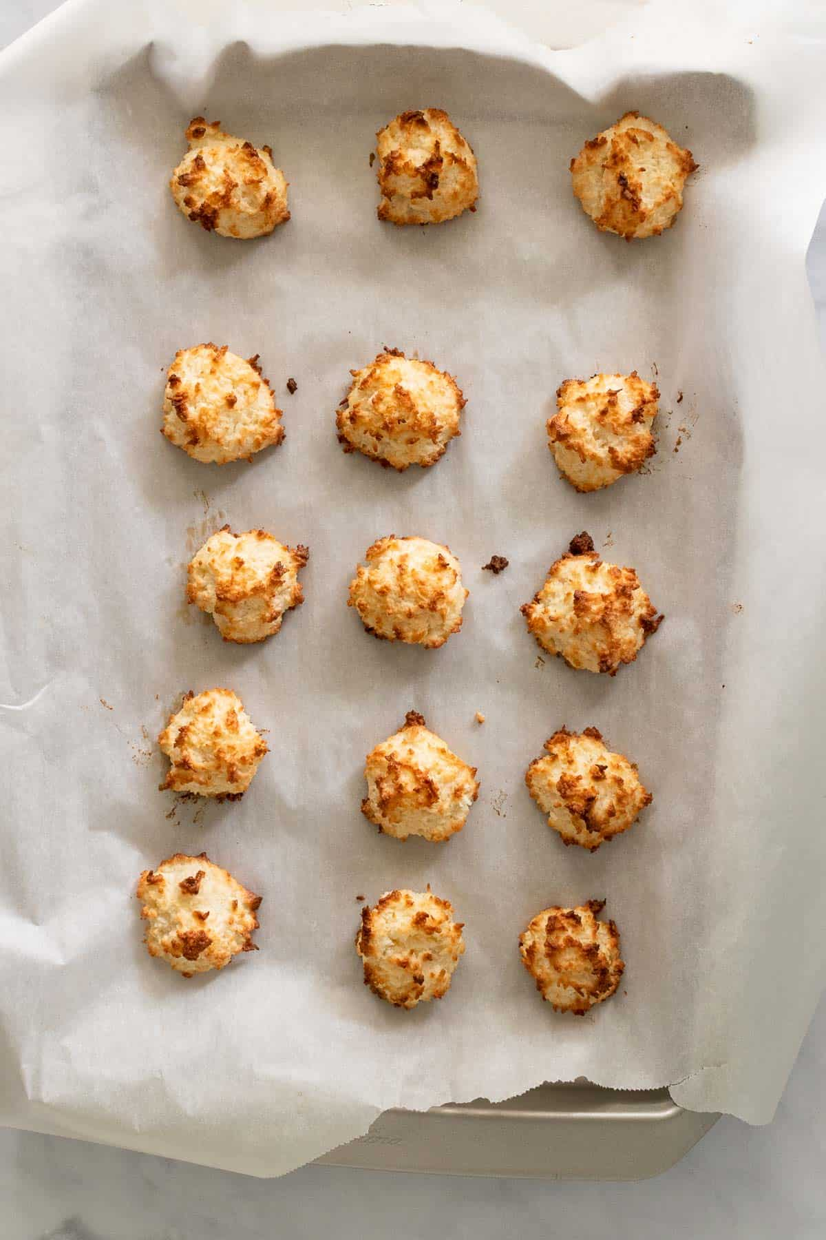 Finished macaroons cooling on a baking sheet lined with parchment paper, as seen from above