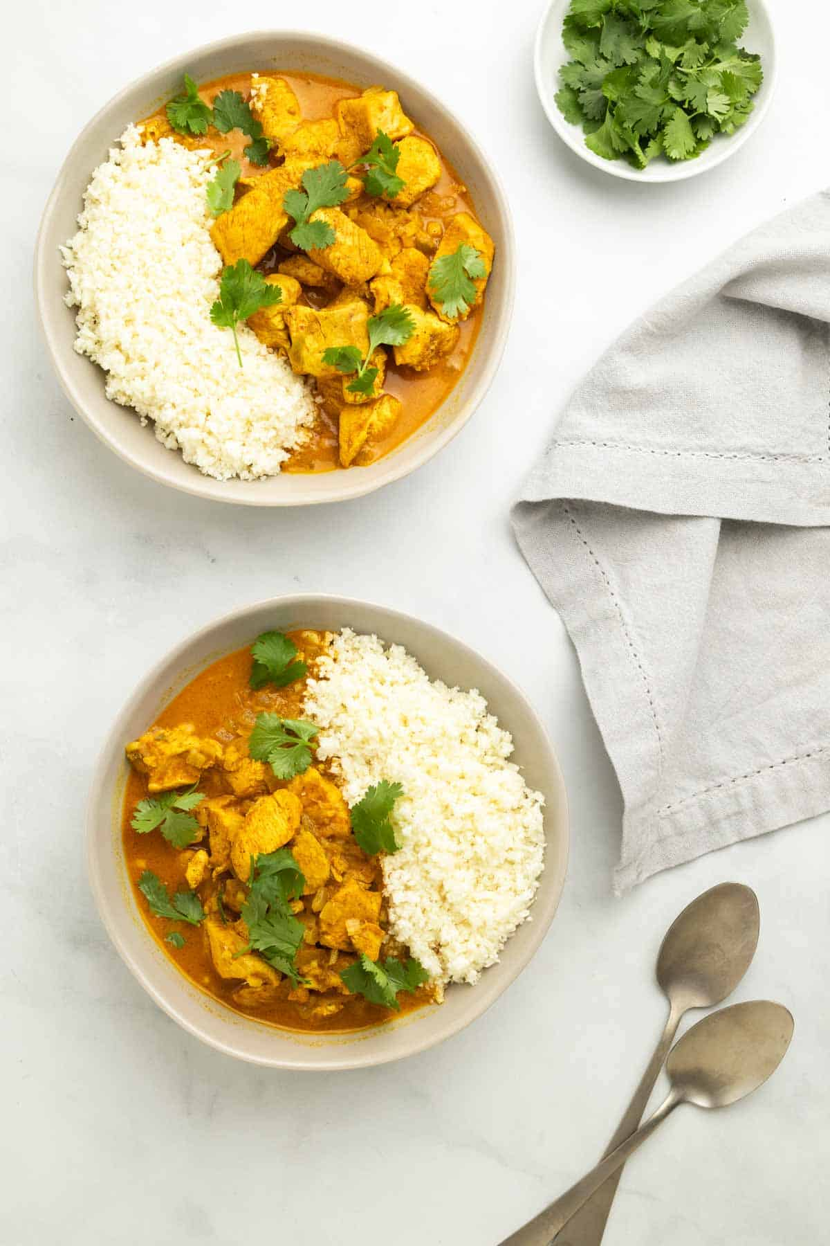 Two bowls of chicken curry served with cauliflower rice and garnished with cilantro