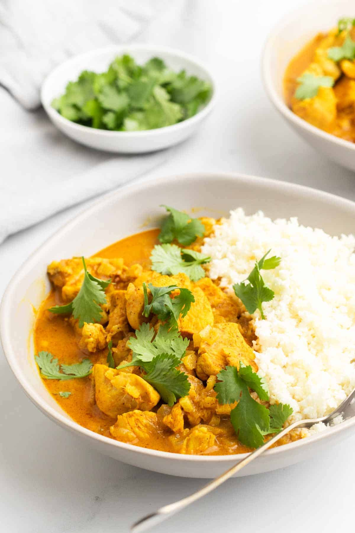 Closeup of chicken curry in a white bowl, garnished with cilantro and served with cauliflower rice