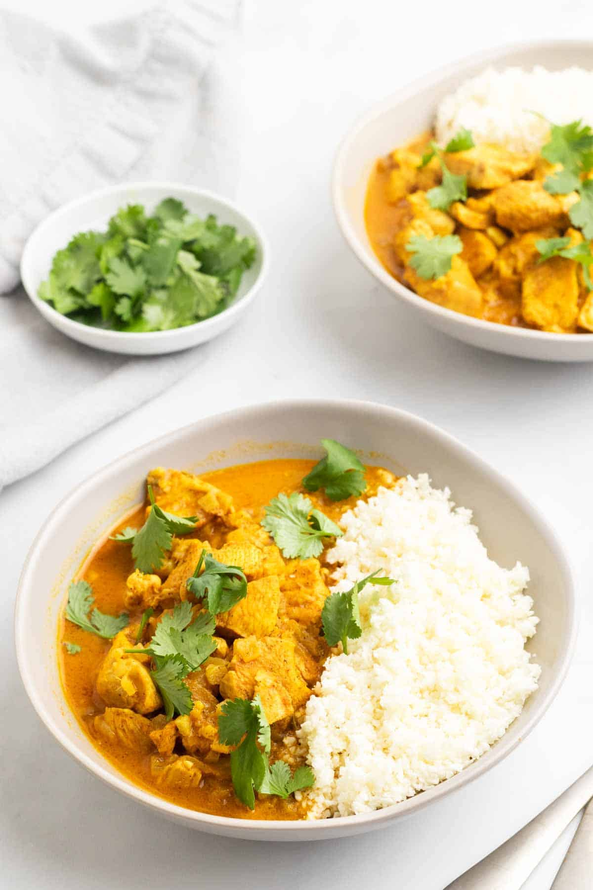 Two bowls of chicken curry with cauliflower rice next to a ramekin of cilantro for garnishing