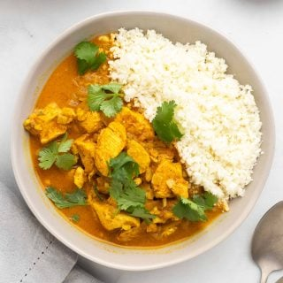 A bowl of keto curry, garnished with cilantro and served with cauliflower rice, as seen from above