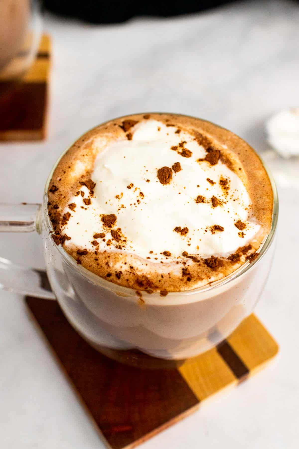 Close-up of hot chocolate in a clear plastic mug, topped with whipped cream and cocoa powder