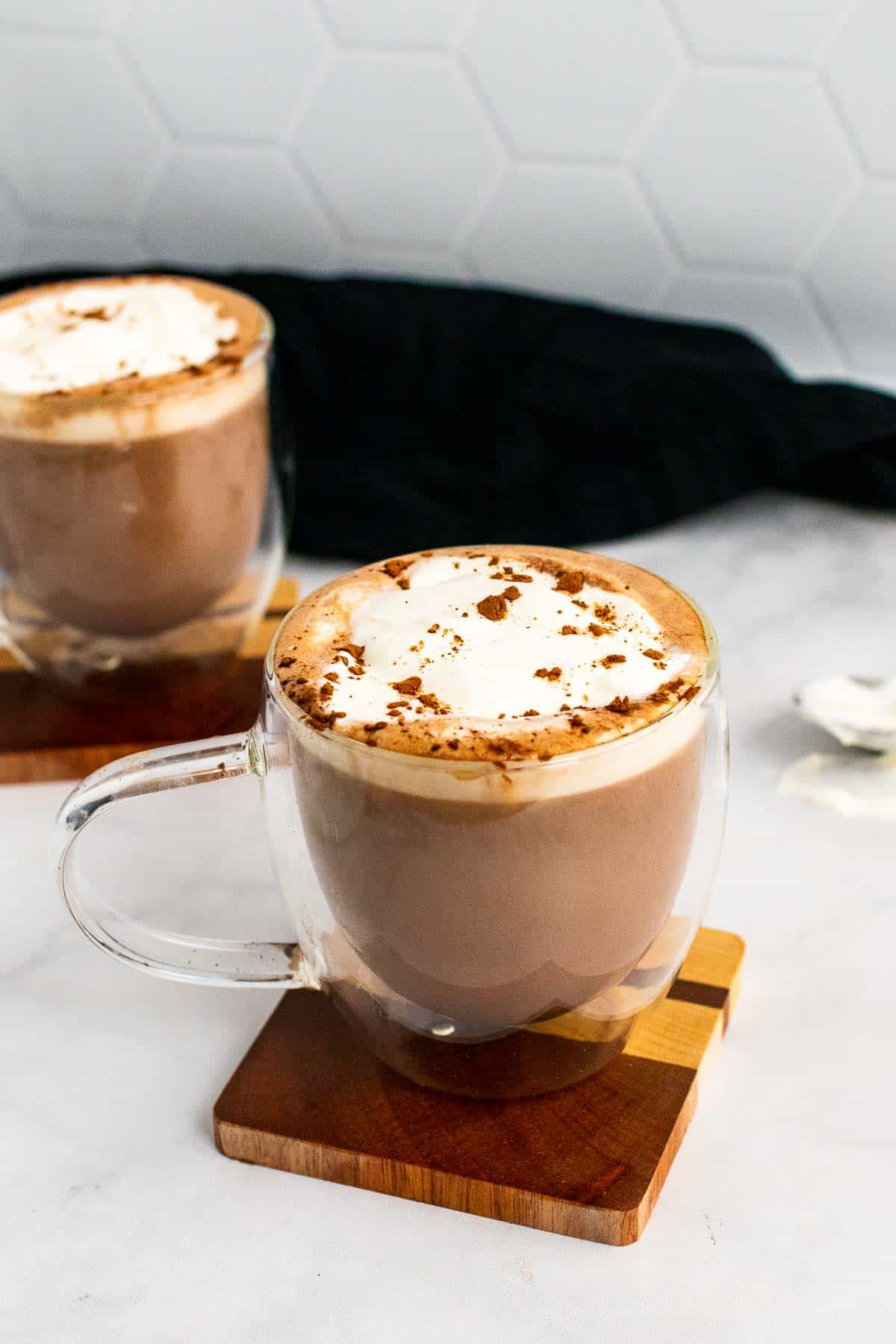 Two mugs of hot chocolate resting on a wooden coaster, topped with whipped cream and cocoa powder