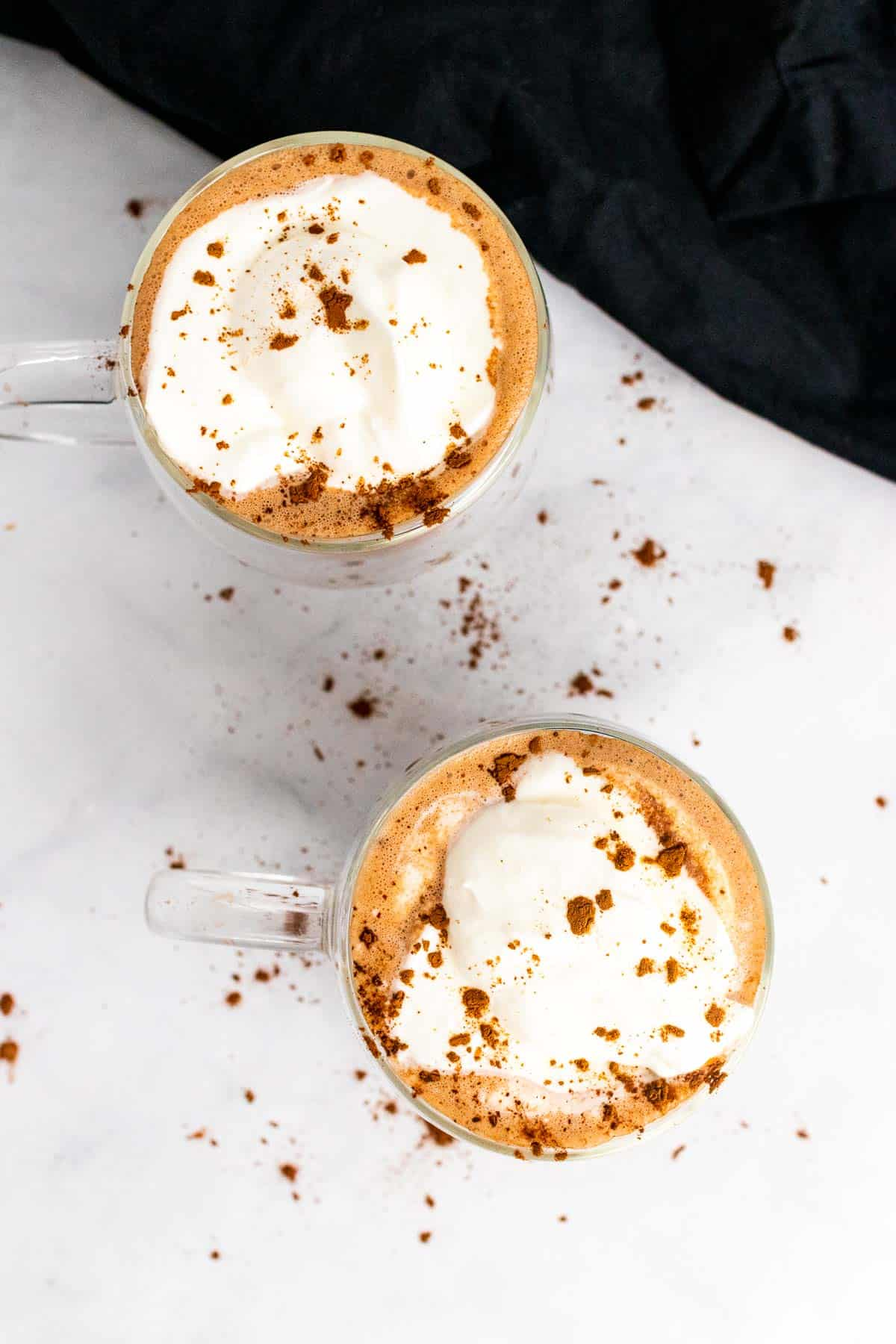 Two mugs of hot chocolate topped with whipped cream and cocoa powder, as seen from above