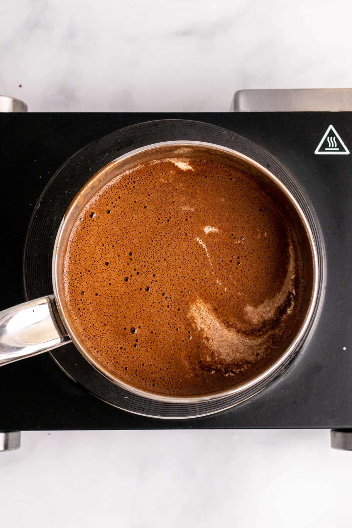 Heavy cream added to the hot chocolate mixture in the pan, as seen from above