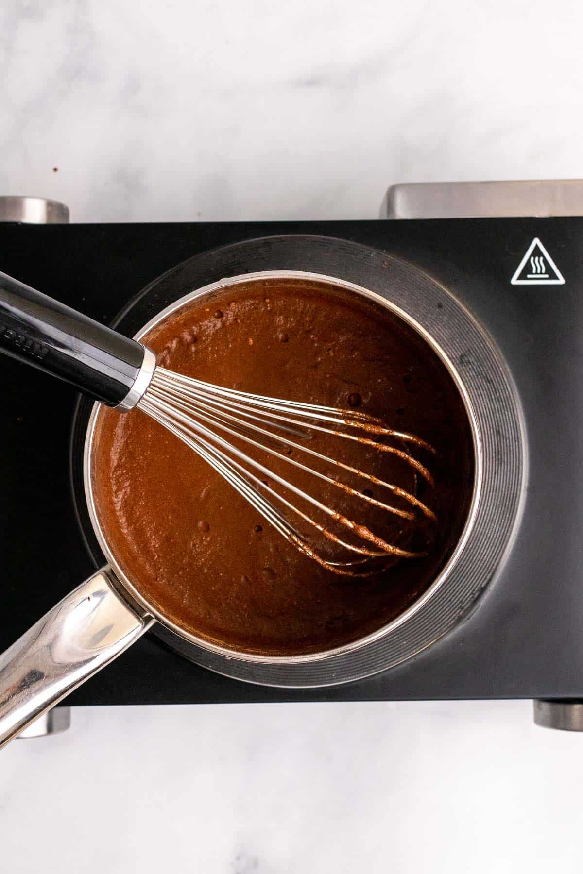 Ingredients combined in a medium saucepan with a whisk, as seen from above