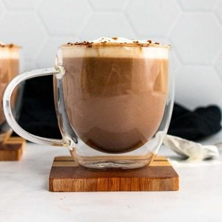 Keto hot chocolate in a clear plastic mug, topped with whipped cream and cocoa powder