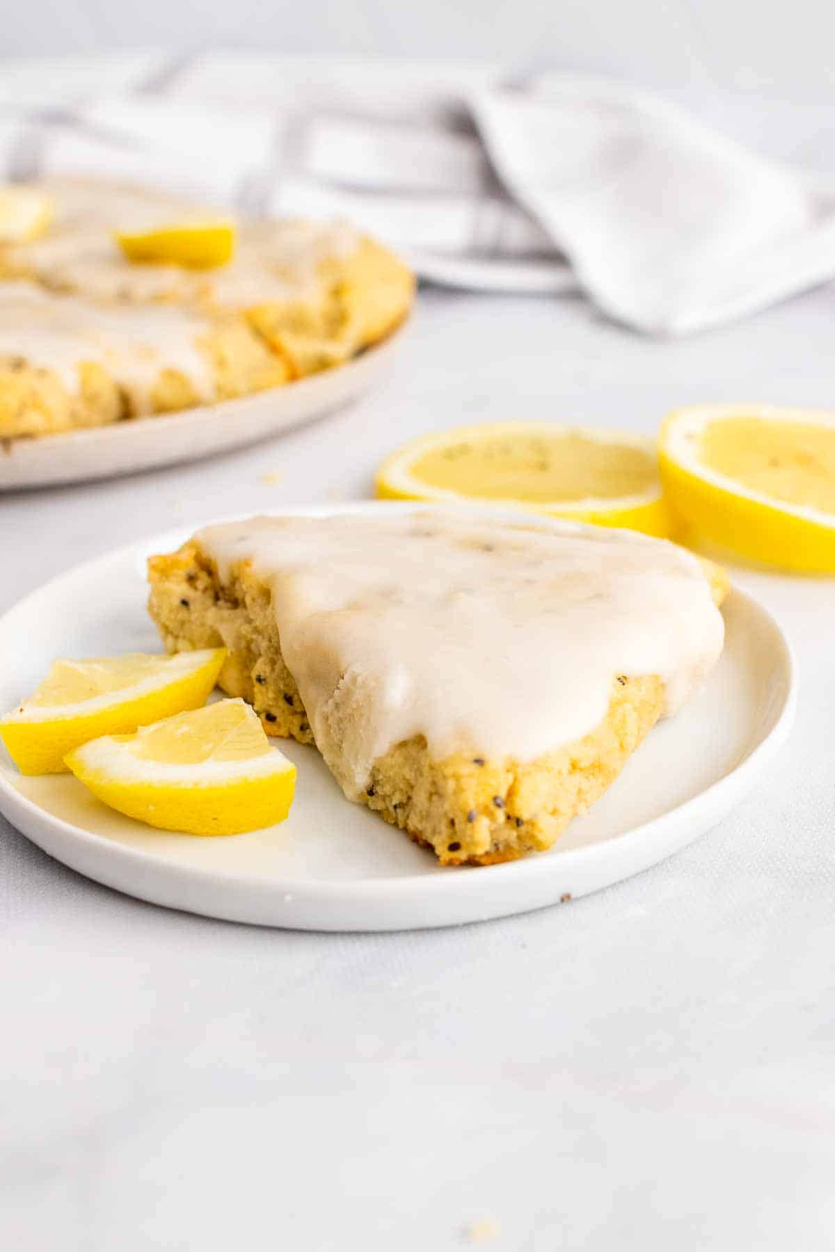 A slice of scone on a white plate next to two quartered lemon slices