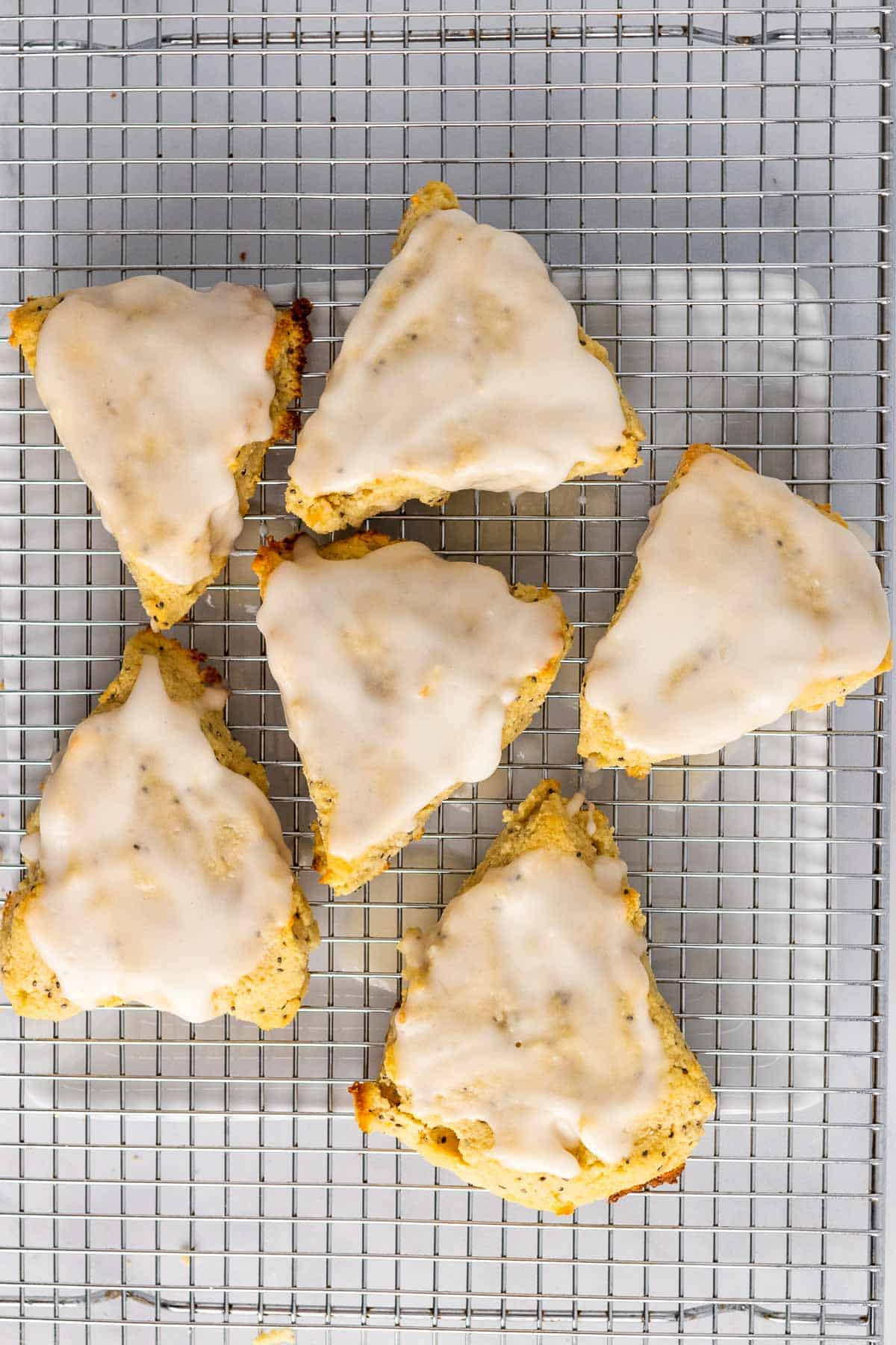 Six scones on a wire cooling rack with lemon glaze added, as seen from above