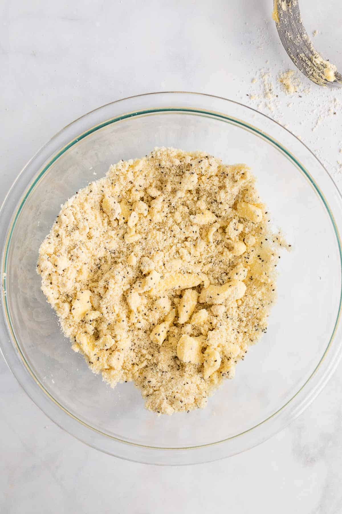 Butter cut into the dry ingredients in a large glass bowl, as seen from above