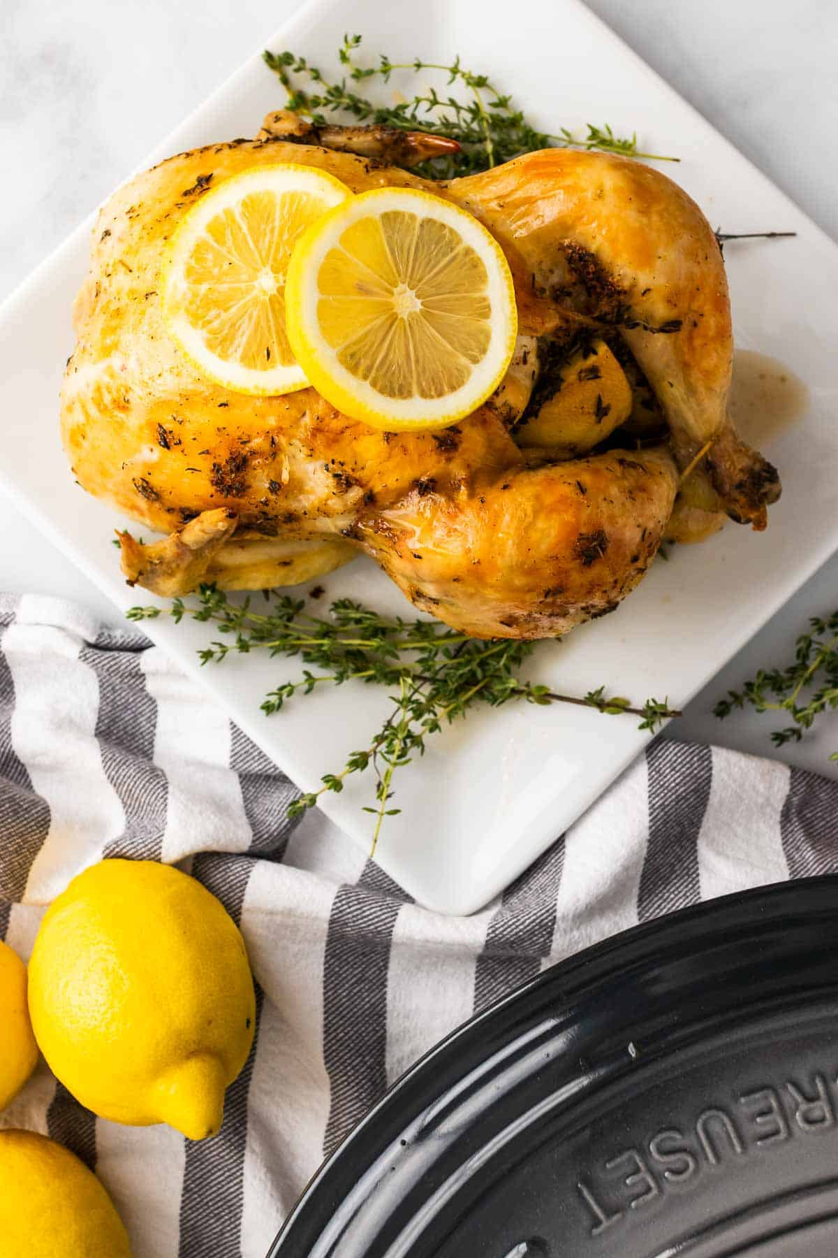 Whole chicken on a white plate next to sprigs of thyme and garnished with two lemon slices, as seen from above