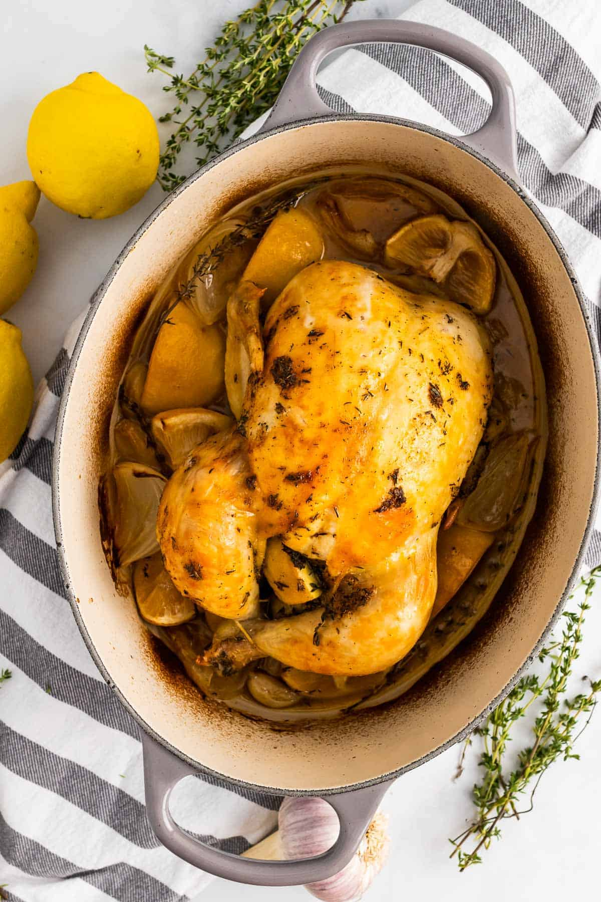 Whole chicken finished cooking and resting in the dutch oven on top of a decorative striped napkin