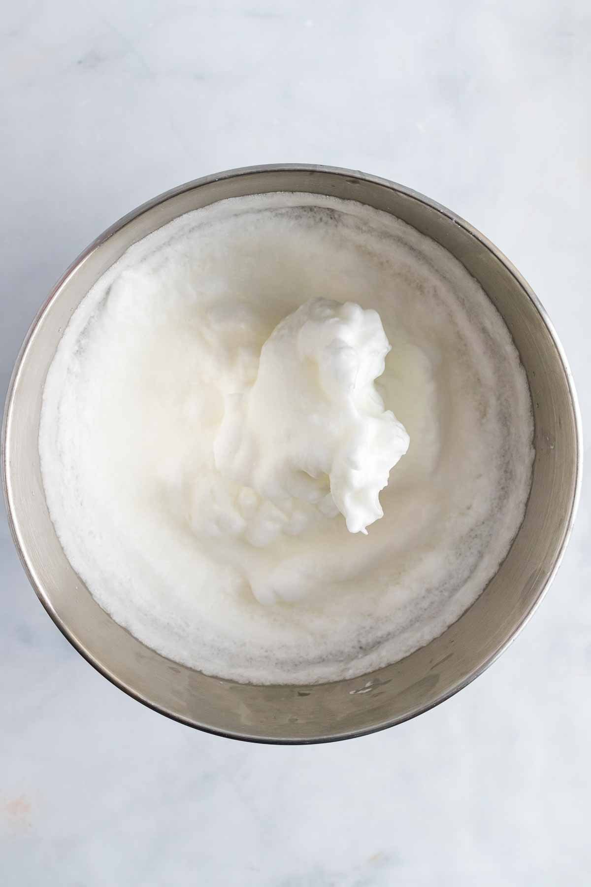 Egg whites beat into stiff peaks in a large mixing bowl, as seen from above