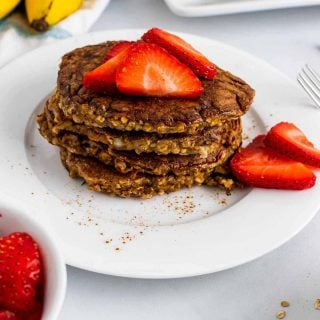 A stack of four flourless banana pancakes on a white plate, topped with and surrounded by strawberry slices