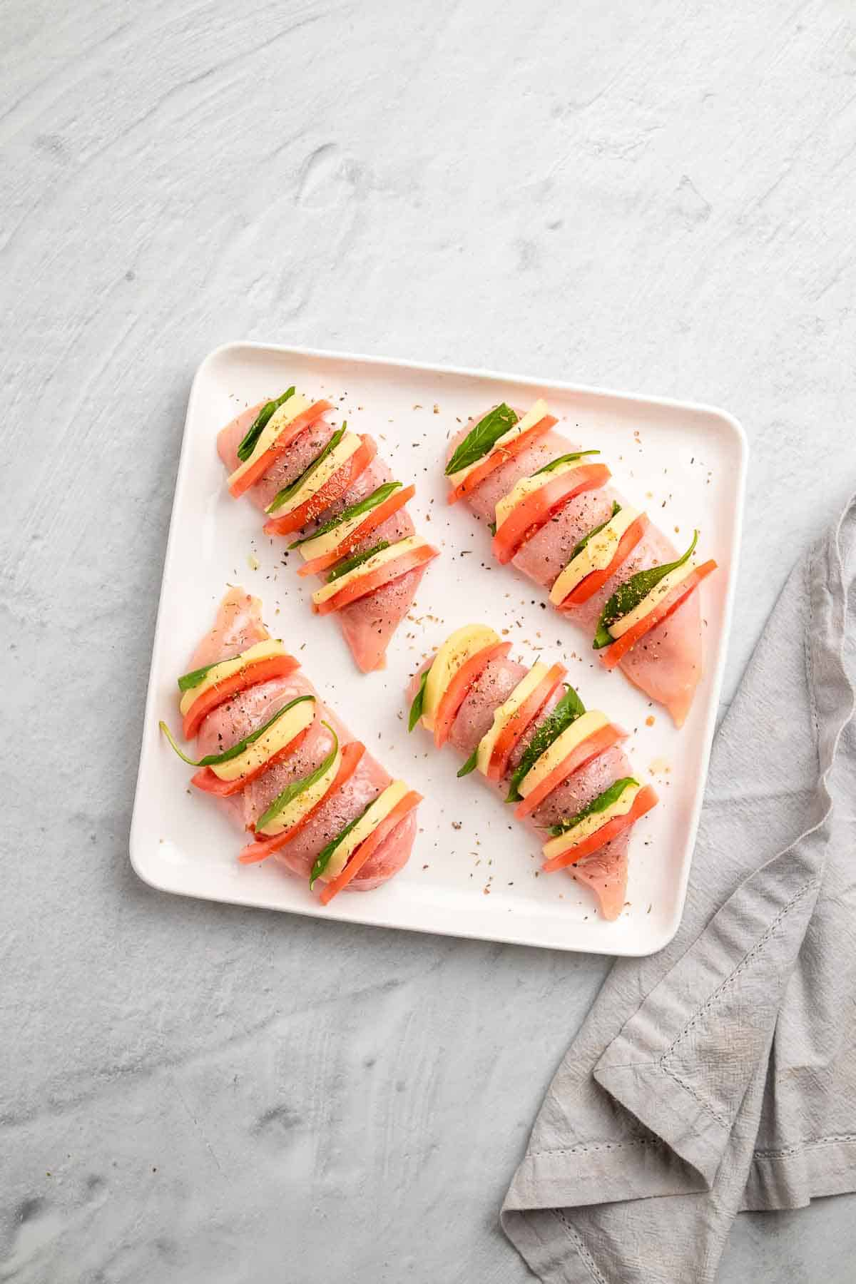 Sliced chicken breasts stuffed with mozzarella, tomato, and basil leaves, topped with salt and pepper