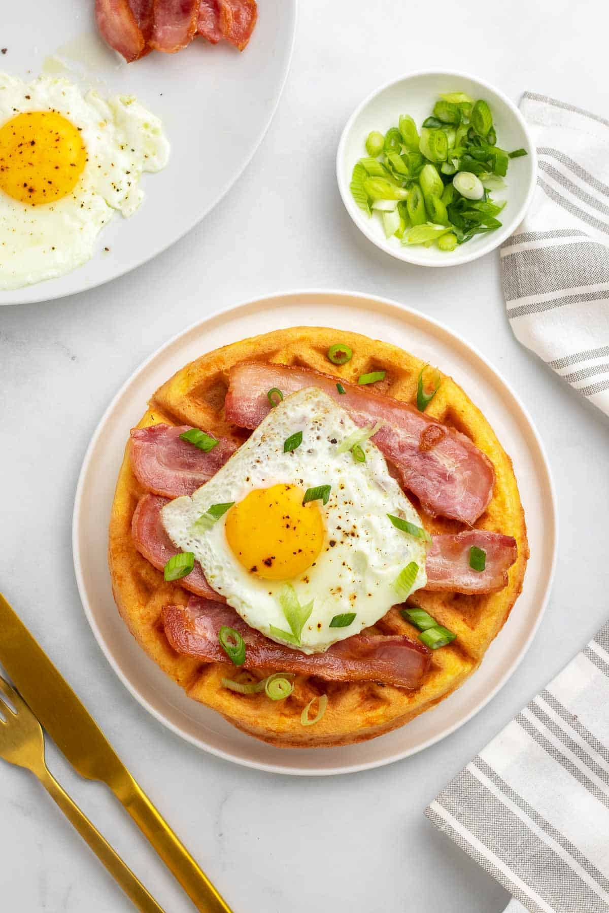 Chaffled topped with bacon, a fried egg, and scallions