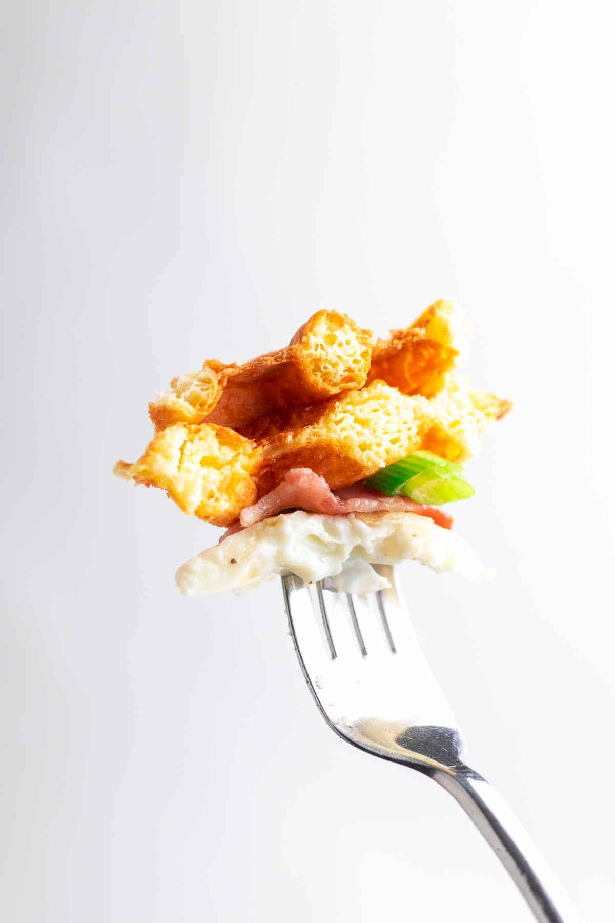 A fork holding a bite of chaffle and toppings in front of white space