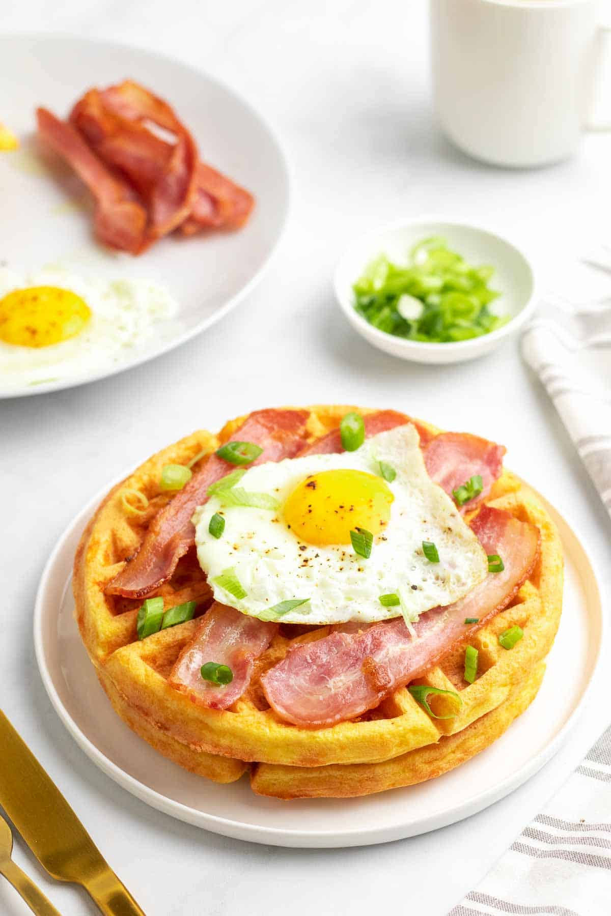 Finished chaffle from Keto Chaffle recipe, topped with bacon, fried egg, and scallions topped with bacon and a fried egg