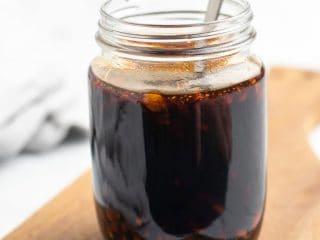 Sugar free teriyaki sauce in a glass mason jar with a metal spoon