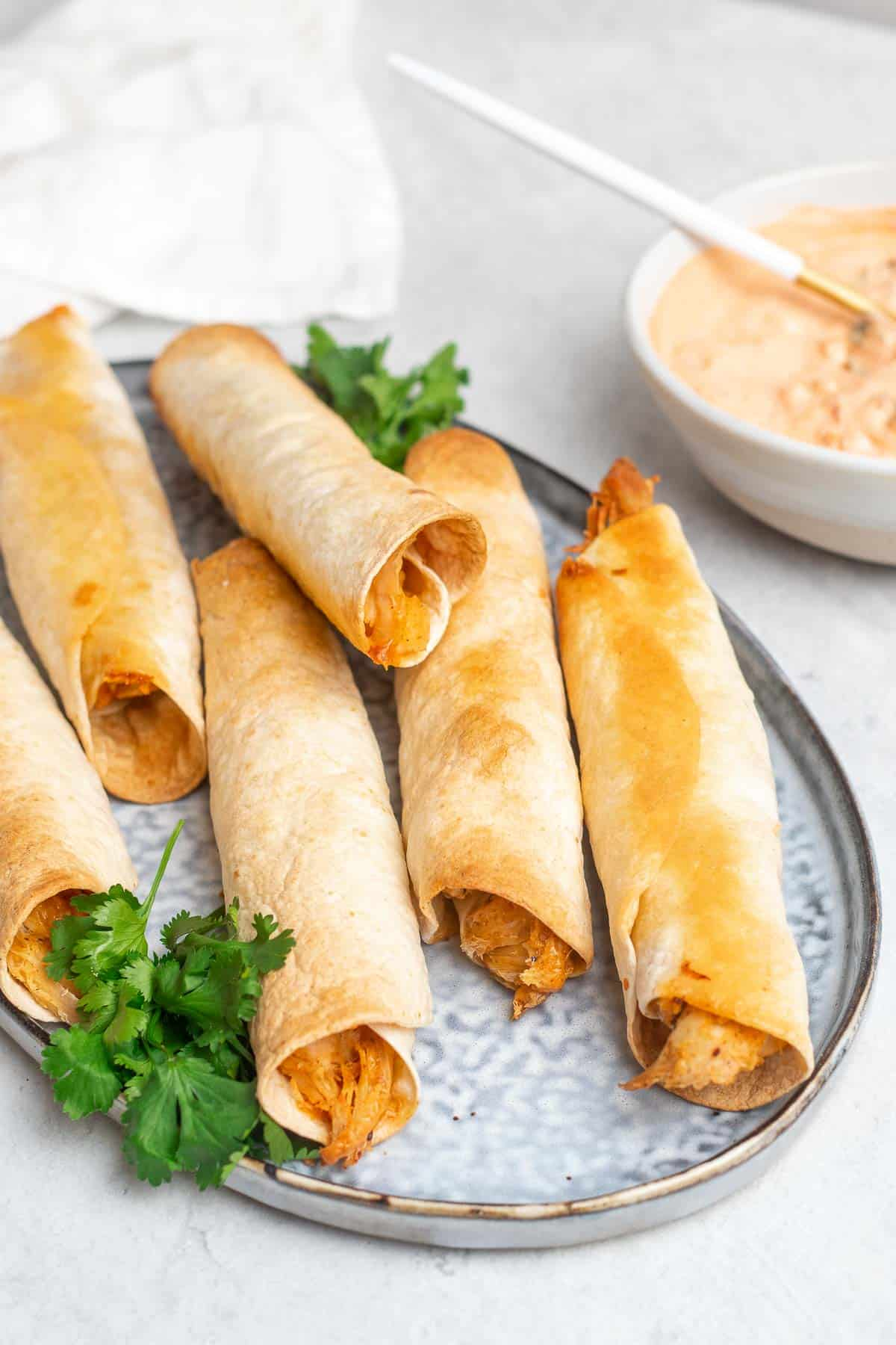 Six baked chicken taquitos on a plate with fresh cilantro next to a white ramekin of sauce
