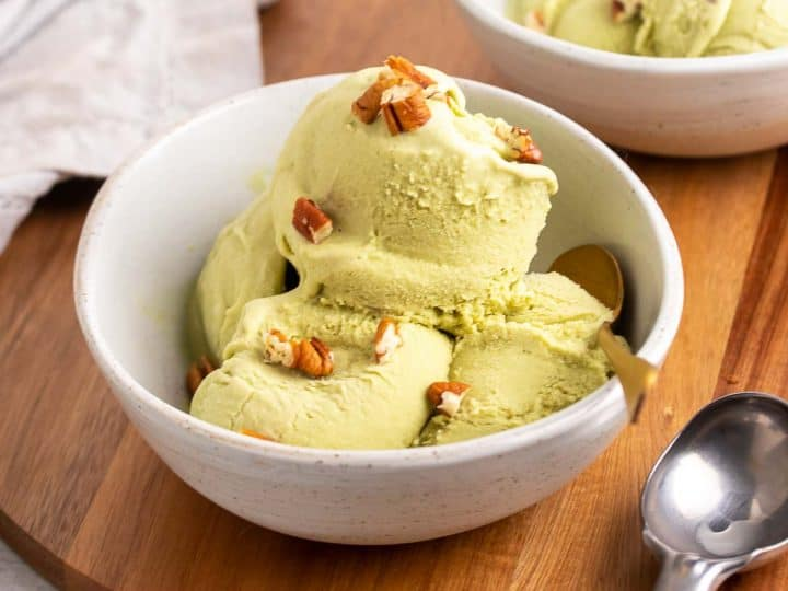 Four scoops of matcha green tea ice cream in a white bowl with a gold spoon, topped with chopped pecans, on a wooden serving tray