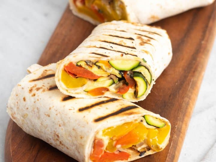 Grilled veggie wraps cut into three halves and placed on a wooden serving tray